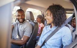 Jeune famille noire dans une voiture sur un sourire de voyage par la route photographie stock