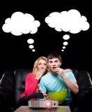 Jeune famille observant un film ou une émission de sport Photos libres de droits
