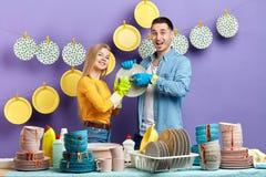 Jeune famille obtenant le plaisir des travaux du ménage photo stock