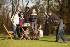 Jeune famille passant le temps sur un pique-nique avec des amis Photos stock