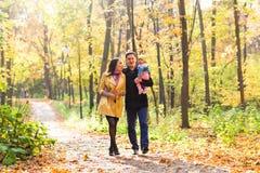Jeune famille pour une promenade en parc d'automne avec Photographie stock libre de droits