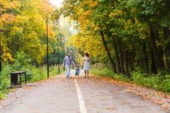 Jeune famille pour une promenade en parc d'automne avec Images stock