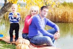 Jeune famille près de lac avec des potirons, temps d'automne Images libres de droits