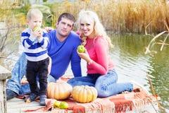 Jeune famille près de lac avec des potirons, temps d'automne Photographie stock