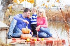 Jeune famille près de lac avec des potirons, temps d'automne Image stock