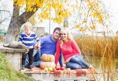 Jeune famille près de lac avec des potirons, temps d'automne Photos stock
