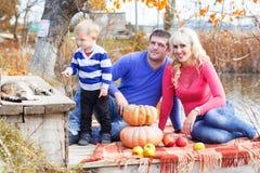 Jeune famille près de lac avec des potirons, temps d'automne Photographie stock libre de droits