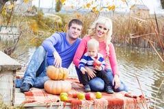 Jeune famille près de lac avec des potirons, temps d'automne Photo libre de droits