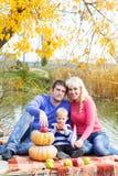 Jeune famille près de lac avec des potirons, temps d'automne Photo stock