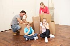 Jeune famille regardant le renversement parmi des cadres Photographie stock