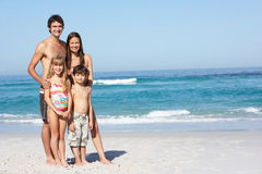 Jeune famille restant sur la plage sablonneuse en vacances Image libre de droits