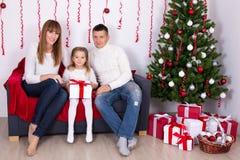 Jeune famille s'asseyant dans le salon décoré avec le tre de Noël Photos stock