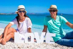 Jeune famille s'asseyant sur la plage avec amour de mot Images libres de droits
