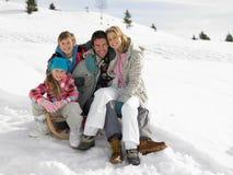 Jeune famille s'asseyant sur un traîneau dans la neige image libre de droits