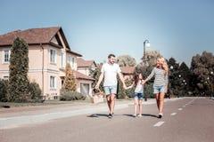 Jeune famille satisfaisante marchant et apportant le panier de produit Photos libres de droits