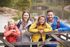 Jeune famille se penchant sur une barrière en bois dans la campagne, regardant la caméra, fin  photo stock