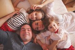 Jeune famille se situant dans le lit à la maison photos libres de droits