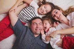 Jeune famille se situant dans le lit à la maison photographie stock