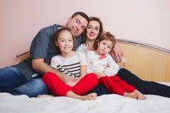 Jeune famille se situant dans le lit à la maison images stock