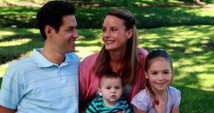 Jeune famille souriant à l'appareil-photo en parc banque de vidéos