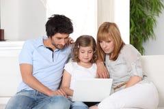 Jeune famille sur le sofa photos stock