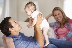 Jeune famille sur Sofa At Home photographie stock libre de droits