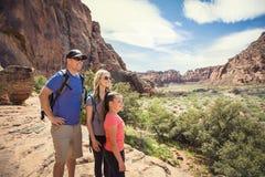 Jeune famille trimardant en beau canyon rouge de roche dans le sud-ouest Etats-Unis image stock