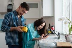 Jeune famille Un homme frotte une tasse jaune, une femme choquée regardant un smartphone, actualités inattendues images libres de droits