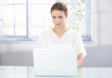 Jeune femelle à l'aide de l'ordinateur portatif à la maison image stock
