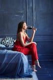 Jeune femelle élégante buvant d'un vin rouge de verre Image stock