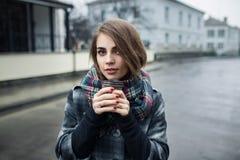 Jeune femelle adulte avec la tasse de café de papier restant sur la rue de ville le jour pluvieux nuageux ; Images stock