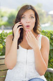 Jeune femelle adulte choquée parlant au téléphone portable dehors Image libre de droits