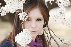 Jeune femelle adulte regardant par des fleurs Photographie stock