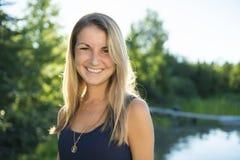 Jeune femelle attirante avec les cheveux blonds posant près du lac photographie stock libre de droits