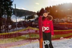 Jeune femelle attirante dans le costume de ski, le casque et les lunettes de ski stan Photographie stock libre de droits