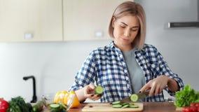 Jeune femelle attirante en gros plan moyenne appréciant faisant cuire la salade saine de légume frais de nourriture clips vidéos