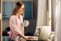 Jeune femelle attracrive se tenant tenante la tasse, dactylographiant sur l'ordinateur portable Photographie stock