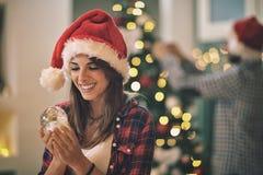 Jeune femelle avec la boule de neige pour Noël Image stock