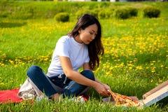 Jeune femelle avec la longue tranche de participation de cheveux de pizza tout en se reposant sur l'herbe et appr?ciant le d?jeun photos stock