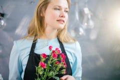 Jeune femelle avec les yeux gris et scintillants avec des fleurs d'intérieur Image stock