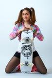 Jeune femelle avec une planche à roulettes Photo stock