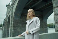 Jeune femelle blonde à la mode dans le manteau sur la rue Images libres de droits
