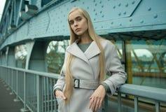 Jeune femelle blonde à la mode dans le manteau sur la rue Photos stock