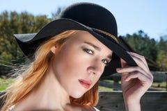 Jeune femelle blonde en portrait de porte de chapeau noir  Photographie stock
