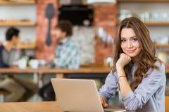 Jeune femelle bouclée positive attirante à l'aide de l'ordinateur portable en café Photos stock