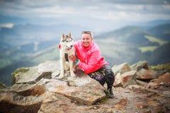 Jeune femelle caucasienne avec le chien de chien de traîneau sibérien Photographie stock libre de droits