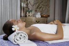 Jeune femelle décontractée obtenant un massage en pierre dans une station thermale image libre de droits
