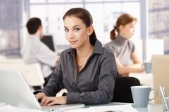 Jeune femelle dans des collègues de bureau travaillant derrière Photographie stock