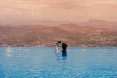 Jeune femelle dans la piscine sur le toit à l'arrière-plan de la ville grecque de Volos au coucher du soleil et aux montagnes Photographie stock libre de droits