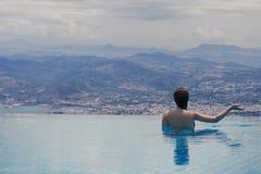 Jeune femelle dans la piscine sur le toit à l'arrière-plan de la ville grecque de Volos au coucher du soleil et aux montagnes Photo stock